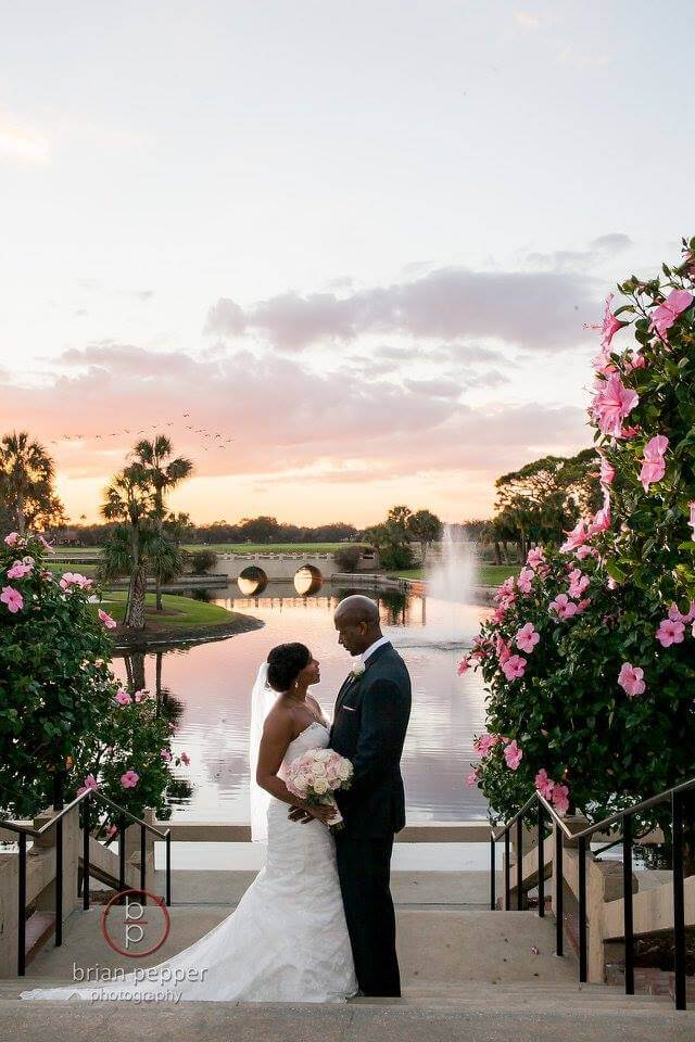Bride and Groom Embracing at Sunset framed by the blooming pink hibiscus trees at Mission Inn