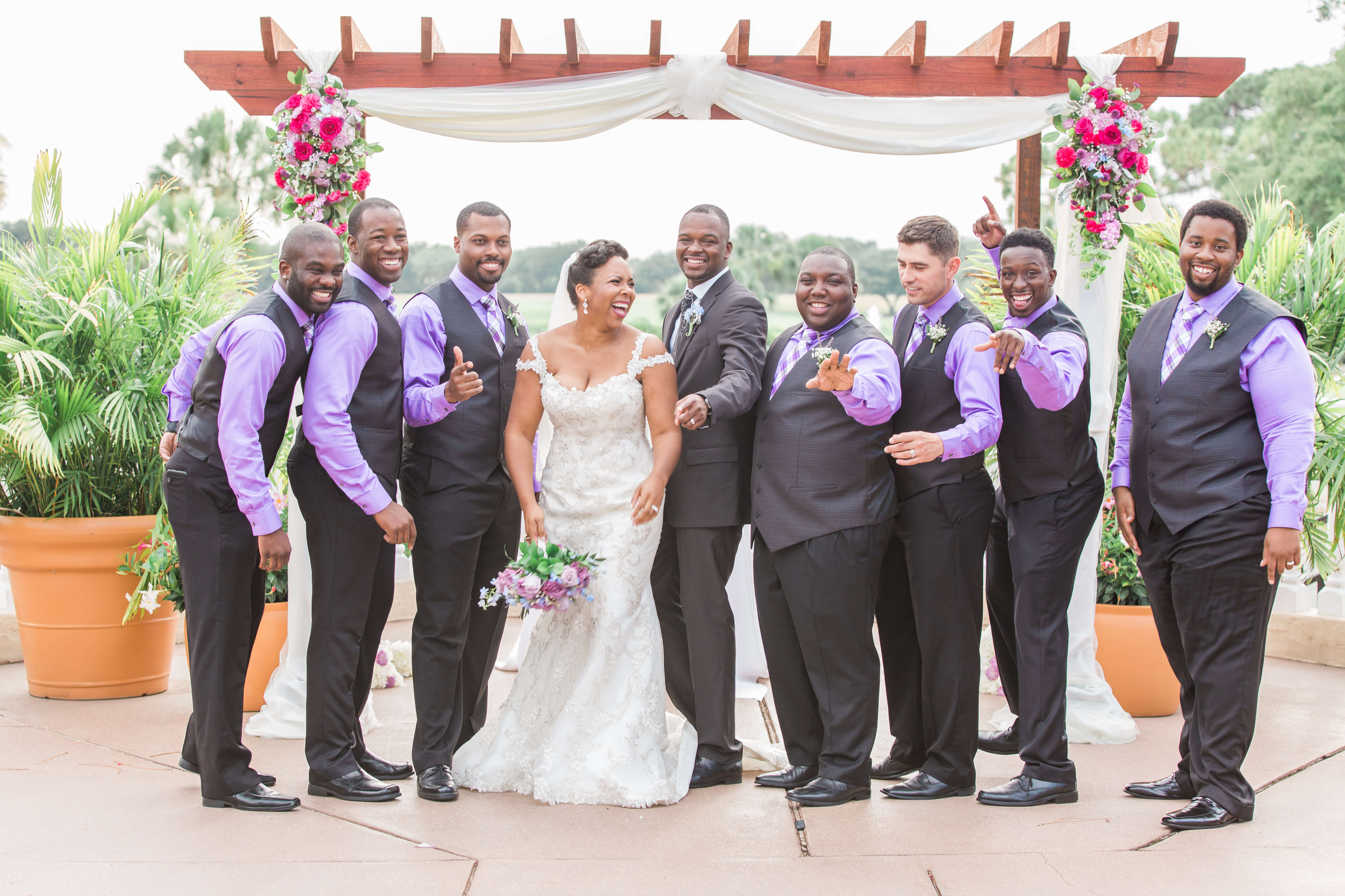 Groomsmen in purple shirts with bride and groom standing in front of arch at Plaza de la Fontana after garden ceremony