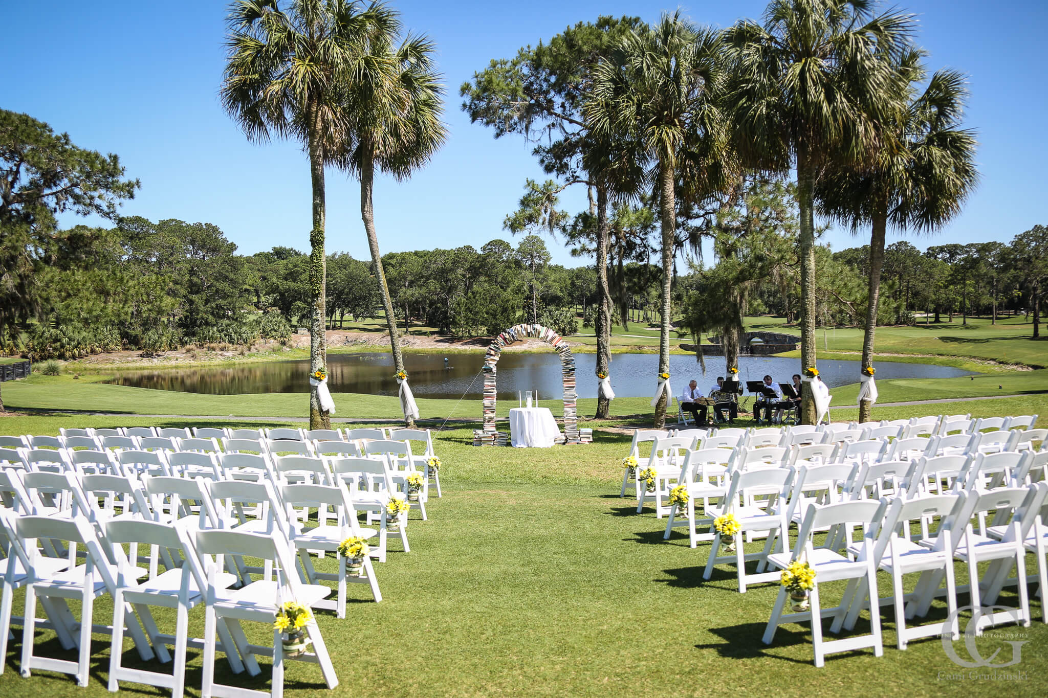 Garden wedding ceremony with golf course backdrop with book arch