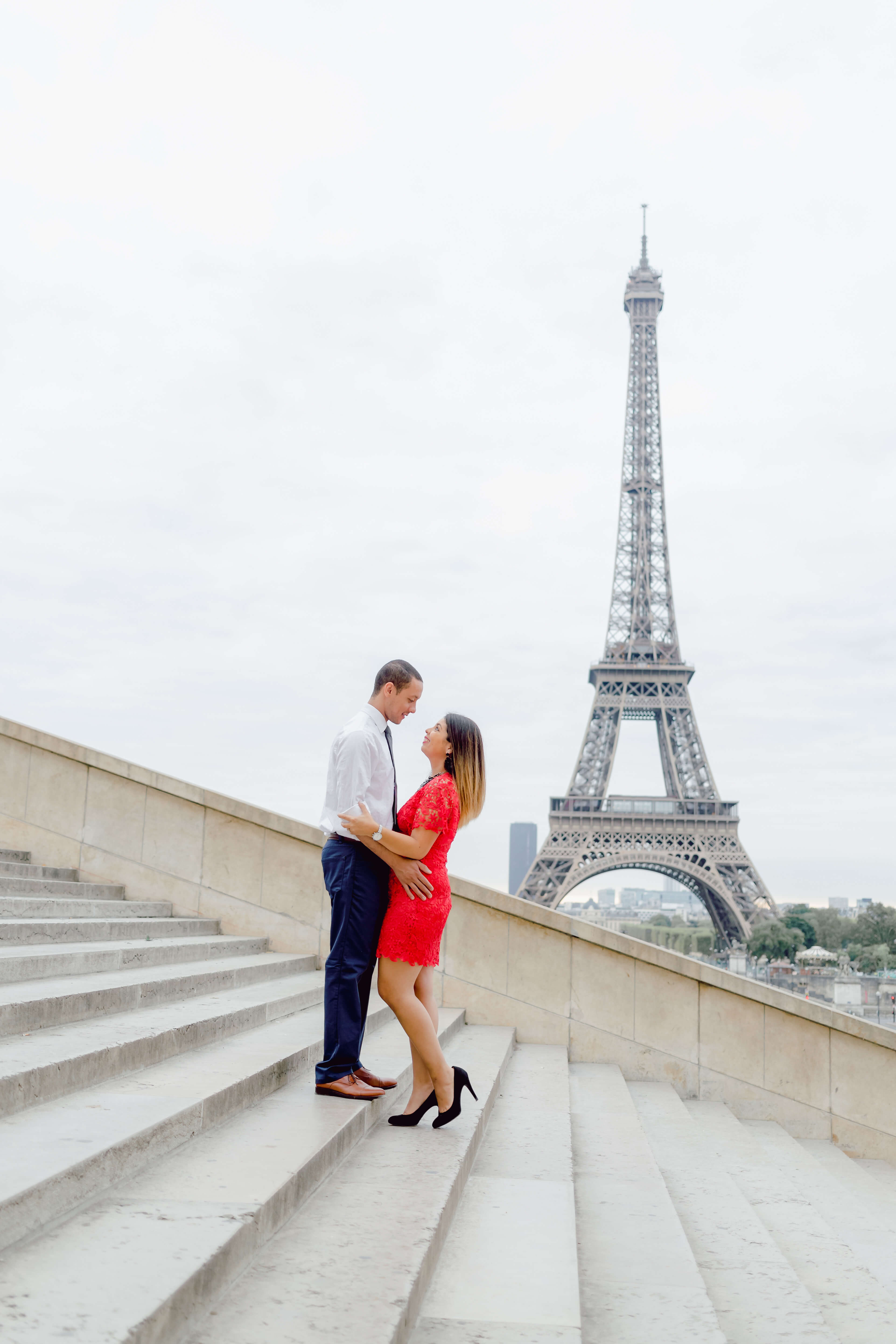 Couple in love on the steps in front of the Eiffel Tower