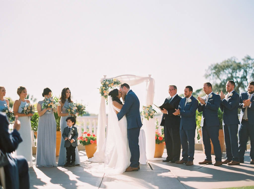 Bride and Groom Kissing at Plaza de la Fontana with arch and bridal party by Katie Rosado